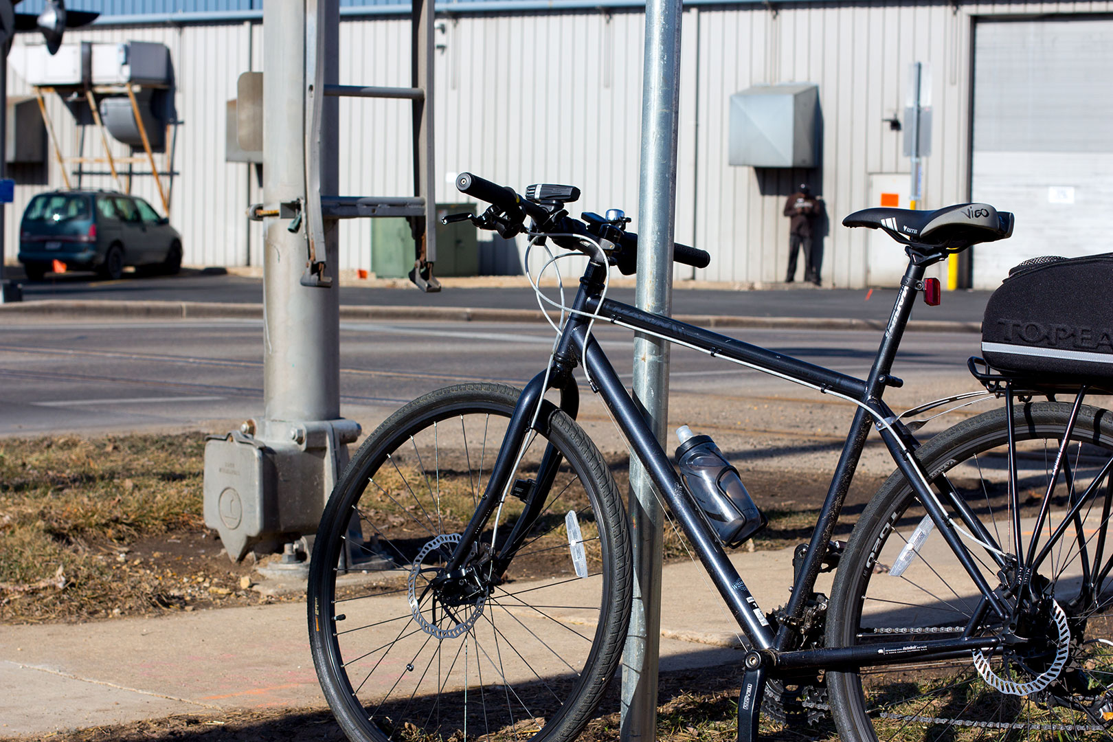 A bike, railroad tracks, a factory and a factory worker